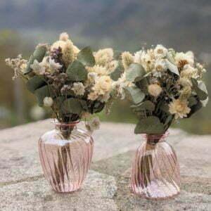 Duo de bouquets de fleurs séchées champêtres dans leurs vases en verre teinté rose pastel
